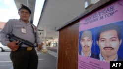 An Indonesian policeman next to a poster of Malaysian fugitive Noordin Mohammed Top, who is allegedly behind a series of suicide bombings in Indonesia dating back to 2003 and is one of Asia's most-wanted and elusive militant leaders.