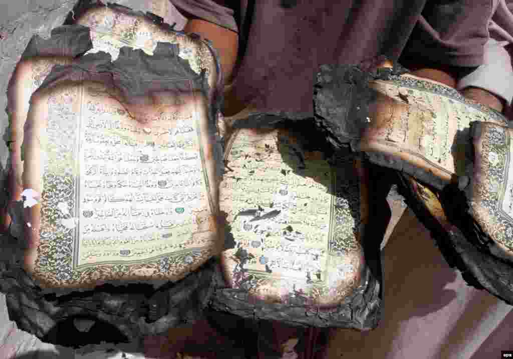 """An Iraqi man displays a Koran destroyed during fighting with insurgent militias in Baghdad in July (epa) - During an interview with RFE/RL's Radio Free Iraq in April, former Iraqi Prime Minister Iyad Allawi warned of the beginning of a """"social split"""" in Iraq that, if unchecked, could lead to """"catastrophe."""""""