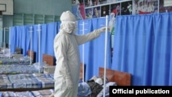 Медработник в защитном костюме оказывает помощь пациенту в стационаре в Бишкеке. Июль 2020 года.