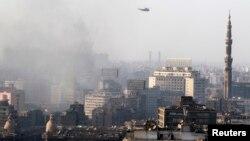 Військовий гелікоптер летить у хмарах диму після сутичок між прихильниками Мурсі і силами безпеки в Каїрі, 16 серпня 2013 року