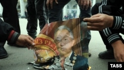 Protesters burn a portrait of ousted Kyrgyz President Kurmanbek Bakiev on the streets of Bishkek on April 8.