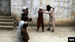 An unidentified militant of Islamic State (IS) imparting light weapons training to children at an undisclosed location in the Kunar province, eastern Afghanistan in July.