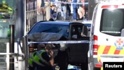 Police sit in front of a crashed vehicle after Saeed Noori, the driver, was arrested after plowing into pedestrians at a crowded intersection in Melbourne in December 2017.