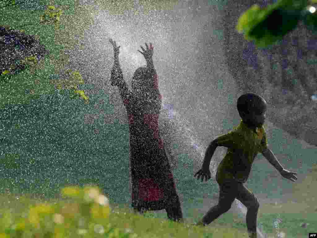 Pakistani children cool off by walking through water sprinklers during a heatwave in Lahore on June 14. Photo by Arif Ali for AFP