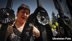 Учасники пікетування зав'язують траурні стрічки на паркані, що огороджує Верховну Раду, Київ, 26 квітня 2012 року