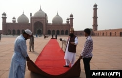Workers roll out a red carpet at the Badshahi Mosque in Lahore, ahead of the royal visit to the historic site on October 17.