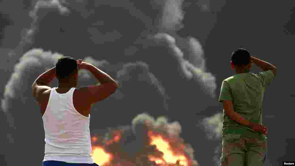 Venezuelans watch fuel storage tanks burn at the Amuay oil refinery in Punto Fijo in the Peninsula of Paraguana. (REUTERS/Stringer)