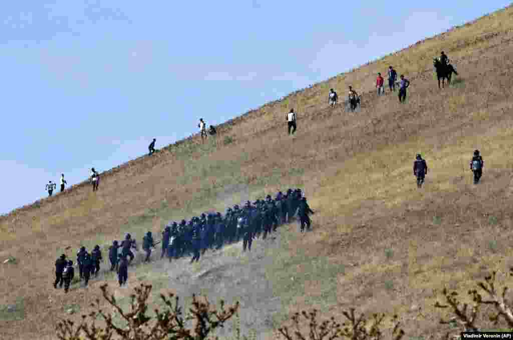 Kyrgyz riot police pursue supporters of former President Almazbek Atambaev near his residence in the village of Koi-Tash, about 20 kilometers south of Bishkek. Police in Kyrgyzstan detained Atambaev following violent clashes with his supporters. He is being charged with corruption. (AP/Vladimir Voronin)