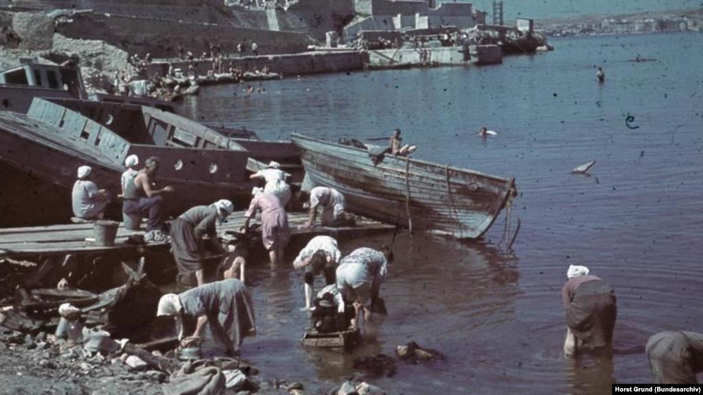 Уцілілим севастопольцям все так само потрібно було готувати їжу і прати одяг. А оскільки майже все місто лежало в руїнах, люди поверталися до старих перевірених практик. На фото: місцеві жінки перуть у Севастопольській бухті, липень 1942 року