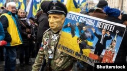 """A demonstrator takes part in a rally demanding """"no capitulation"""" to Russia in Kyiv on December 8, 2019."""