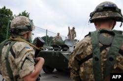 Яворівський полігон. Українські солдати спостерігають за американськими військовослужбовцями, які в свою чергу вивчають український бронетранспортер
