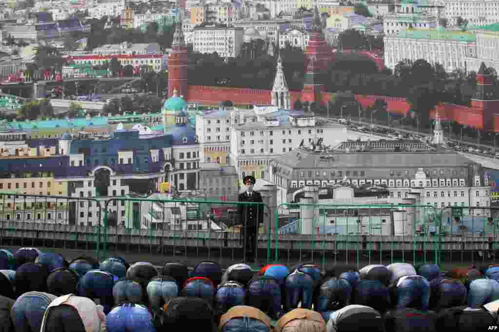 A police officer stands guard in front of a banner depicting Moscow's panorama as Muslims pray on a street in Moscow during the Eid al-Adha festival. (AFP)