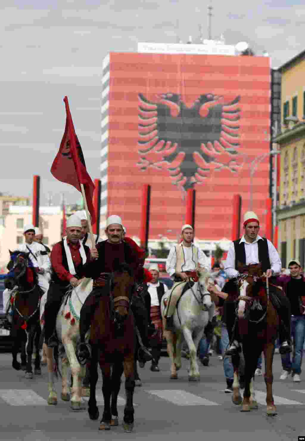 Kosovar Albanian men wear traditional attire as they ride through Tirana.