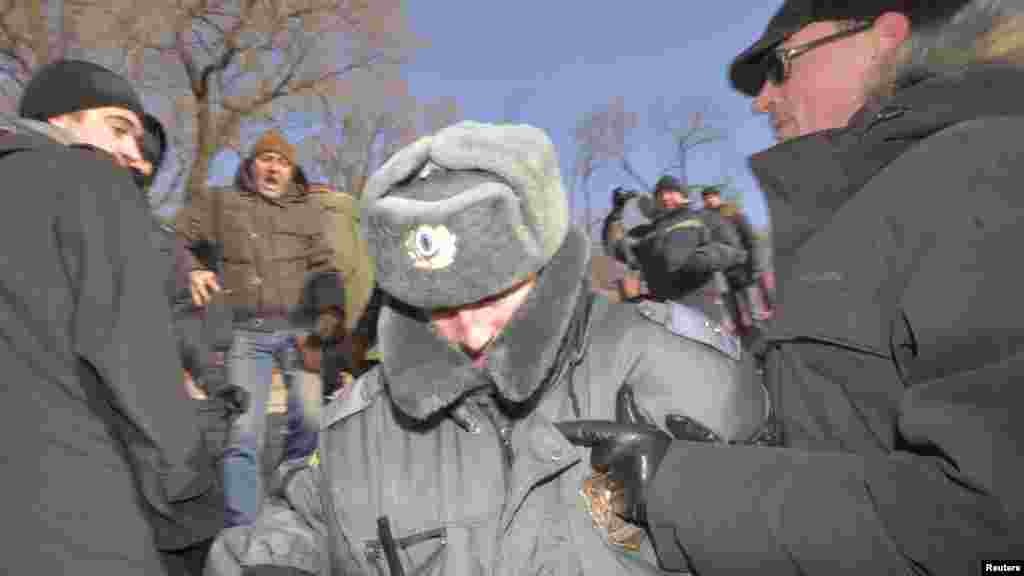 A policeman tries to escape from demonstrators during a protest in the far eastern city of Vladivostok.