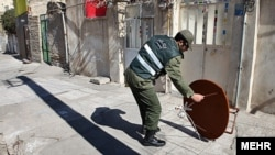 Iranian police remove satellite dishes from roofs in east Tehran in late February.