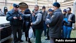 Российские полицейские проверяют документы у мигрантов из Таджикистана.