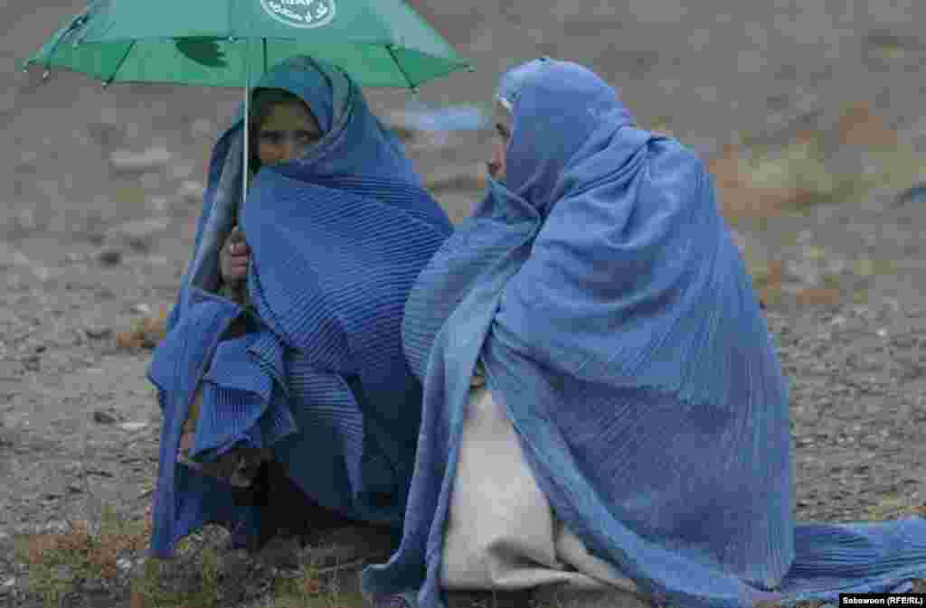 Rain is no deterrent for women waiting to pick up rations.