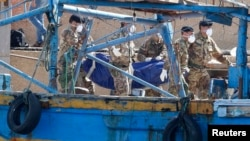 Италия сарбаздары кеме апатында қаза болған адамның денесін алып барады. Лампедуза аралы, 6 қазан 2013 жыл. (Көрнекі сурет)
