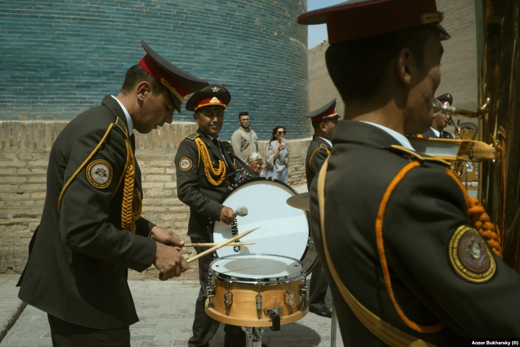 A military band performs at the base of a minaret in Khiva.