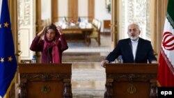 Федеріка Моґеріні (л) поправляє незвичну, але обов'язкову для жінки в Ірані хустку на прес-конференції з Могаммадом Джавадом Заріфом (п), Тегеран, 28 липня 2015 року