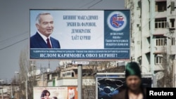 People walk in front of an election poster for Uzbek President Islam Karimov in Tashkent last week.