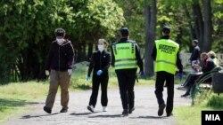 Илустрација - Луѓе со заштитни маски и полиција во Градски парк во Скопје