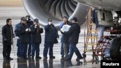 Эксперты несут в руках батарею самолета Boeing 787 Dreamliner, совершившего аварийную посадку. Такамацу, 17 января 2013 года. Фото с сайта агентства Рейтер.