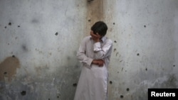 A young man stands weeping near a wall damaged by shrapnel from a bomb attack in Peshawar in January.