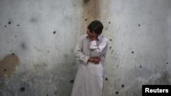 Një i ri qëndron pranë murit ku shihen gjurmët e shpërthimit