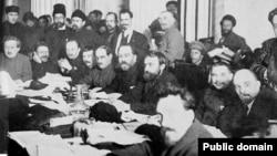 نشست رهبران حزب بلشویک. نشسته از چپ: آول اینوکیتزه، میخائیل کالینین، نیکلای بوخارین، میخائیل تومسکی، میخائیل لاشهویچ، لو کامنف، یوگنی پریوبراژنسکی، لئونید سربریاکوف، ولادیمیر لنین و آلکسی ریاکوف – اکثر این افراد در دوره قدرت استالین با تبعید یا زندان و اعدام روبهرو شدند.
