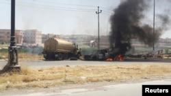Горящая техника иракских сил безопасности в городе Мосул, 10 июня 2014.