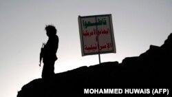 یک عضو حوثیها در کنار شعارنوشتههایی در مورد آمریکا و اسرائیل در پنجمین سالگرد شورش این گروه و تصرف پایتخت؛ صنعا، ۳۰ شهریور