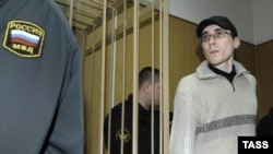 Roman Popkov is escorted into the defendants' cage before a session at a court in Moscow in March 2008.