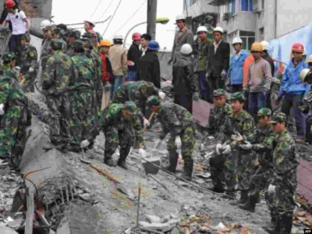 China -- Soldiers clear rubble from a collapsed building a day after a 7.8 magnitude earthquake hit the town of Mianzhu in Sichuan Province, 13May2008