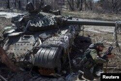 Проросійський бойовик біля підбитого українського танка у селищі Спартак, березень 2015 року