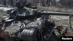 Пророссийский сепаратист рядом с искореженным танком украинской армии. Поселок Спартак Донецкой области, 16 марта 2015 года.
