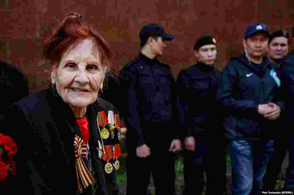 Пожилая женщина, вероятно ветеран тыла, на фоне сотрудников спецназа. Алматы, 9 мая 2019 года.
