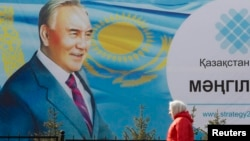 Kazakhstan -- A woman walks past a poster depicting Kazakh President Nursultan Nazarbaev in Almaty, February 16, 2015