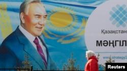 Kazakhstan -- A woman walks past a poster depicting Kazakh President Nursultan Nazarbaev in Almaty, February 16, 2015