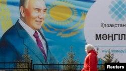 Женщина проходит рядом с билбордом с изображением президента Казахстана Нурсултана Назарбаева. Алматы, 16 февраля 2015 года.