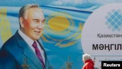 Қазақстан президенті Нұрсұлтан Назарбаевтың суреті бар жарнама қасынан өтіп бара жатқан әйел. Алматы, 16 ақпан 2015 жыл.