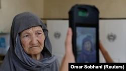کارمند کمیسیون انتخابات حین گرفتن عکس یک رأی دهنده توسط دستگاه بیومتریک در یکی از مراکز رایگیری در کابل. September 28, 2019