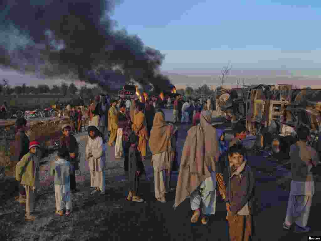 Pakistan residents stand near fuel trucks that were set ablaze in the Bolan district of Balochistan Province in December.
