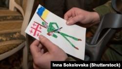 Грузинський доброволець, який воює на боці України у нинішній війні з Росією, тримає дитячий малюнок. Київ, 8 лютого 2015 року