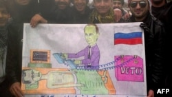 Syrians in the northwestern town of Kfar Nubul pose with a cartoon depicting Russia's Vladimir Putin defibrillating Syrian President Bashar al-Assad by using a veto to block a UN resolution against Assad.