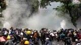 A rendőrség könnygázzal támadja a katonai puccs ellen tüntetőket Mandalajban, 2021. március 3-án.