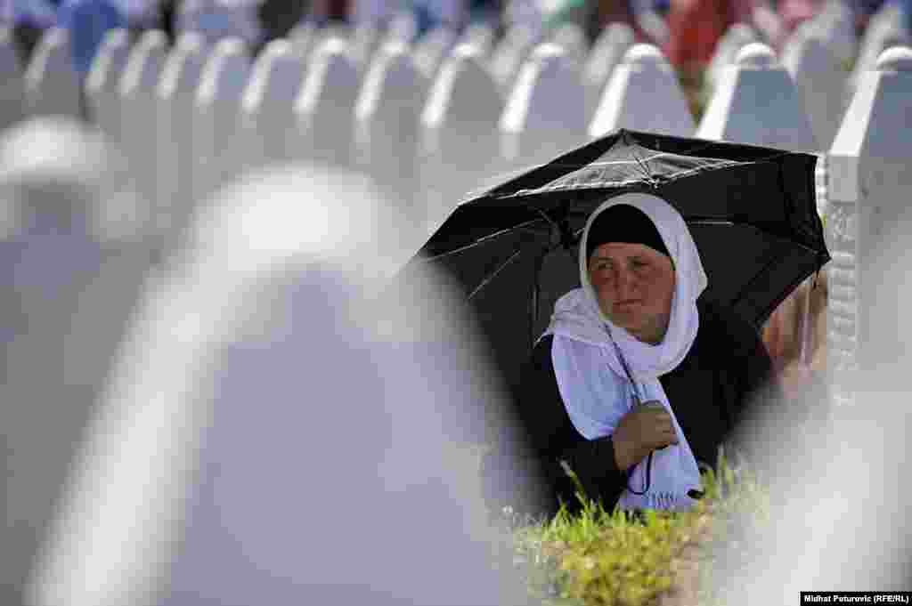 A woman mourns on July 11 at the Potocari memorial for victims of the 1995 massacre in Srebrenica, Bosnia-Herzegovina. During the 1992-95 war in Bosnia, the United Nations set aside Srebrenica as a safe haven for civilians. But on July 11, 1995, Bosnian Serb troops overran the town and killed about 8,000 Muslim men and boys in the days that followed. (RFE/RL/Midhat Poturovic)