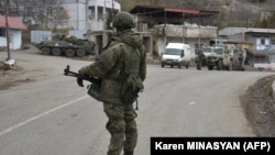 A Russian peacekeeper stands guard on a road in the town of Lachin in December 2020.