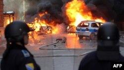 Босния полицейлері үкіметке наразылармен қақтығыс кезінде отқа оранған әкімшілік ғимараттарға қарап тұр. Сараево, 7 ақпан 2014 жыл.