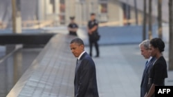 Президент Барак Обама, биринчи леди Мишель Обама жана мурдагы президент Жорж Буш он жыл мурдагы терракт болгон жерде 11-сентябрь курмандыктарын эскерүүдө. Нью-Йорк, 2011-жылдын 11-сентябры.